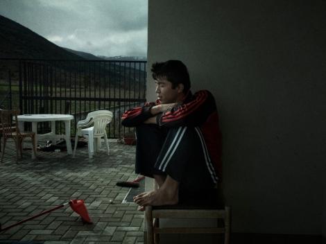 Ali, un chico afgano, sentado en la terraza de la comunidad. De la serie Suspensión. © Álvaro Deprit