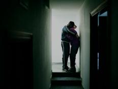 Dos chicos se abrazan en el pasillo de la casa. De la serie Suspensión. © Álvaro Deprit