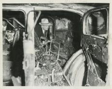 Fotógrafo desconocido: El detective Art Madzinski inspecciona un Yellow Cab que se encontró quemado en la esquina de las avenidas Hoyne y Ogden. El conductor huyó. 1937. Gelatina de plata. © Bogommir Ecker