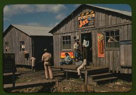 """Barracas y """"juke joint"""" (bar y colmado) para trabajadores inmigrantes, en temporada de poco trabajo. Belle Glade, Florida. Febrero de 1941. LC-USF35-173"""