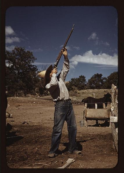 """Fotógrafo: Russell Lee (1903-1986). El señor Leatherman, propietario de una finca, disparando a los halcones que han estado """"robando"""" sus gallinas. Pie Town, New Mexico. Octubre de 1940. LC-USF35-322"""