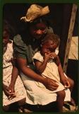 """Fotógrafo: Marion Wolcott (1910-1990). Tres """"Negro children"""" sentados en el soportal de una casa en la plantación Bayou Bourbeau, una cooperativa de la Farm Security Administration situada en las afueras de Natchitoches, Louisiana. Agosto de 1940."""