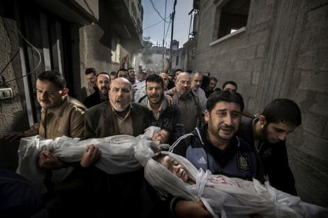 World Press Photo of the Year 2012 Paul Hansen, Suecia, Dagens Nyheter 20 de noviembre de 2012, Ciudad de Gaza, Territorios Palestinos. Suhaib Hijazi,de 2 años de edad, y su hermano mayor Muhammad murieron cuando su casa fue destruida por el impacto de un misil israelí. Su padre, Fouad, también murió, miestras que su madre fue llevada a cuidados intensivos. Los hermanos de Fouad llevan a los niños a la mezquita para la ceremonia de entierro; el cuerpo del padre es llevado más atrás, sobre una camilla.