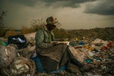 """1st Prize Contemporary Issues Single Micah Albert, USA, Redux Images, 03 de abril de 2012, Nairobi, Kenia. Haciendo una pausa bajo la lluvia, una mujer que trabaja recogiendo basura en el vertedero de más de 70 hectáreas, que literalmente se desborda sobre las casas de un millón de personas que viven en las barriadas cercanas, desearía tener más tiempo para hojear los libros que encuentra. Le gustan hasta los catálogos de piezas industriales. """"Me da algo más que hacer durante el día, además de recoger (basura)"""", dijo."""