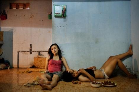 """1st Prize Contemporary Issues Stories Maika Elan, Vietnam, Most """"La elección rosa"""", Vietnam 22 de junio de 2012, Da Nang, Vietnam. Phan Thi Thuy Vy y Dang Thi Bich Bay, que han vivido juntas durante un año, se relajan viendo la televisión después de la escuela. Vietnam ha sido históricamente contrario a las relaciones del mismo sexo, pero el gobierno comunista está considerando reconocer el matrimonio homosexual, algo que sería el primer país asiático en hacer. En agosto de 2012, se realizó en hanoi el primer desfile público del orgullo gay."""