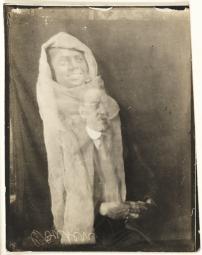 Un hombre y el espíritu de su ayudante. La imagen de la cara de un hombre joeven aparece destacada sobre el hombre, envuelta en una mantilla. El hombre tenía vínculos con la persona que recopiló las fotos del álbum de los espíritus y le dió la fotografía como recuerdo. Aparentemente, había reconocido la cara del joven.