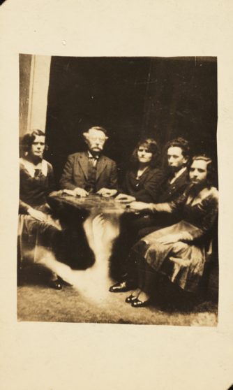 William Hope. Una sesión. 1920. Fotografía de una sesión espiritista, realizada por William Hope alrededor de 1920. La informacion que acompaña el álbum afirma que la mesa está levitando. En realidad, la imagen de un brazo fantasmal ha sido sobrepuesta usando una doble exposición.