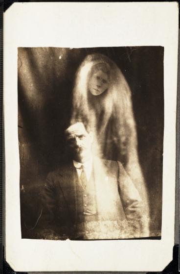 Un hombre con el espíritu de su segunda esposa. La cara de una mujer aparece envuelva en ropas difuminadas alrededor del hombre. El 6 de mayo de 1923, una voz oída en una sesión le dijo que le hicieran la fotografía. Este hombre también había identificado el espíritu de su primera esposa en una fotografía anterior.